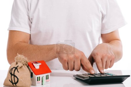 cropped view of man calculating near moneybag and house model isolated on white, mortgage concept