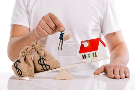 partial view of man holding keys near moneybags and house model on scales isolated on white, mortgage concept