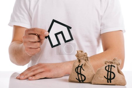 cropped view of man holding paper house near moneybags isolated on white, mortgage concept
