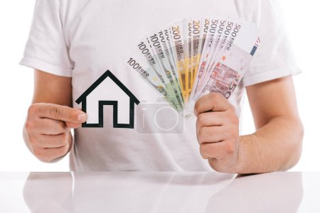 cropped view of man holding cash and paper house isolated on white, mortgage concept