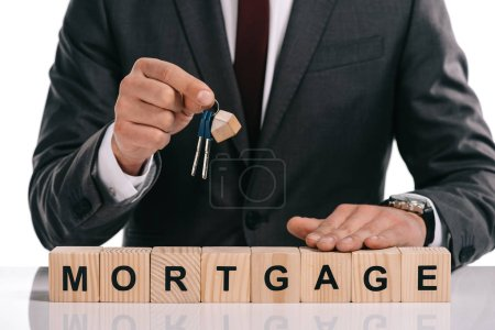 Photo for Cropped view of businessman holding keys near wooden cubes with mortgage lettering isolated on white - Royalty Free Image