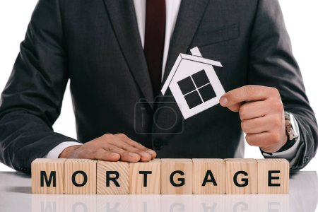 cropped view of businessman holding paper house near wooden cubes with mortgage lettering isolated on white