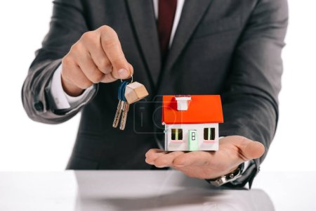 cropped view of mortgage broker holding house model and keys isolated on white