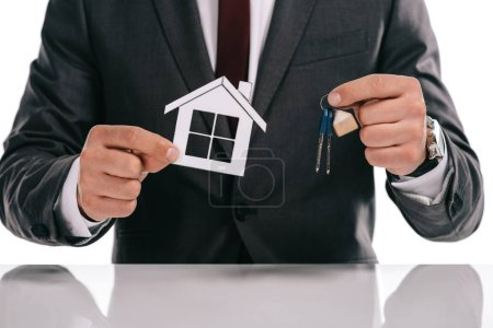 cropped view of mortgage broker holding paper house and keys isolated on white