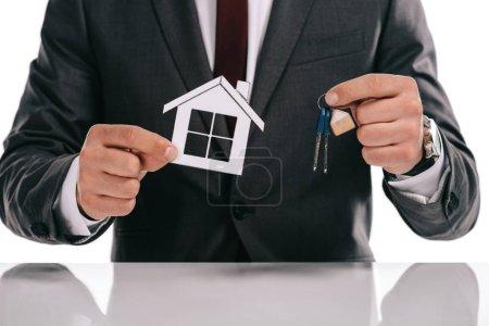 Photo pour Vue recadrée de courtier en hypothèques tenant maison de papier et touches isolés sur blanc - image libre de droit