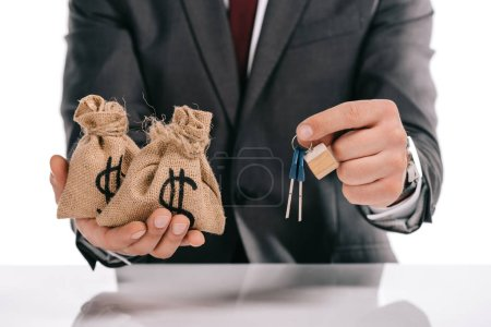 cropped view of mortgage broker holding keys and moneybags isolated on white