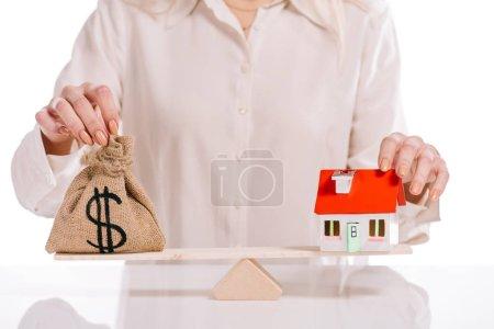 Photo pour Recadrée vue de femme d'affaires pesant la maison modèle et escarcelle isolé sur blanc, hypothèque concept - image libre de droit