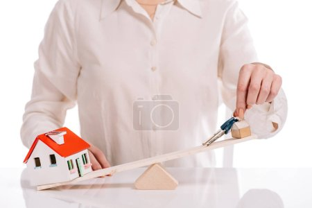 cropped view of businesswoman weighing house model and keys isolated on white, mortgage concept