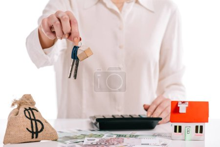 cropped view of businesswoman holding keys near moneybag isolated on white, mortgage concept