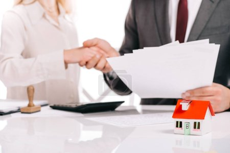 cropped view of businessman and businesswoman shaking hands isolated on white, mortgage concept