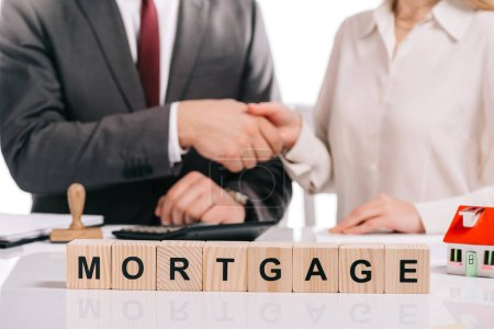 cropped view of businessman and businesswoman shaking hands near wooden cubes with letters isolated on white, mortgage concept