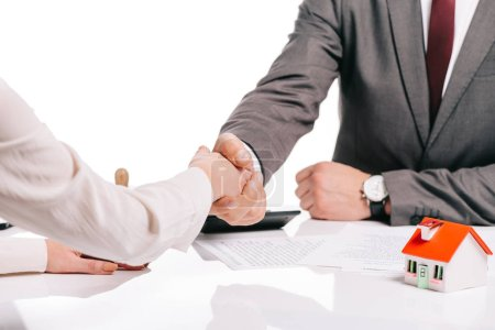 cropped view of businessman and woman shaking hands isolated on white, mortgage concept