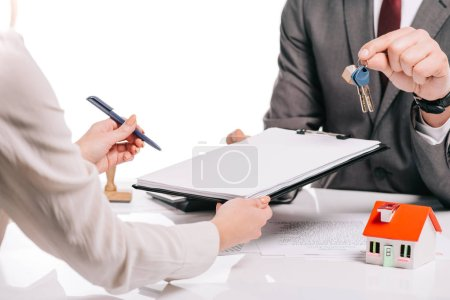 cropped view of mortgage broker and woman making deal and holding keys isolated on white, mortgage concept