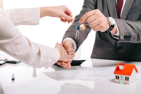 Photo pour Recadrée vue de courtier en hypothèques serrant la main de la femme et en maintenant les touches isolés sur blanc, hypothèque concept - image libre de droit