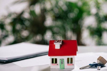 selective focus of house model near keys on white desk, mortgage concept