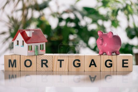 selective focus of house model and piggy bank on wooden cubes with letters, mortgage concept