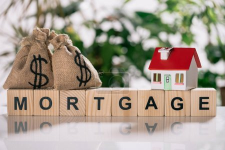 Photo for Selective focus of moneybags with dollar signs and house model on wooden cubes with letters, mortgage concept - Royalty Free Image