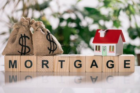 selective focus of moneybags with dollar signs and house model on wooden cubes with letters, mortgage concept