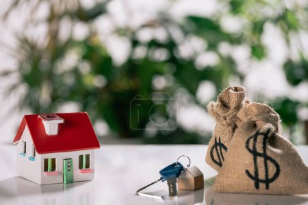 selective focus of keys, house model and moneybags with dollar signs on white desk, mortgage concept