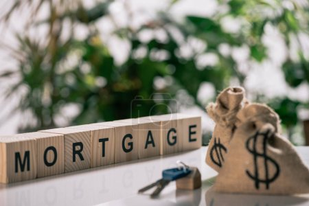 Foto de Enfoque selectivo de las llaves, saquitos con signos de dólar en el escritorio blanco, concepto de hipoteca y cubos de madera con letras - Imagen libre de derechos
