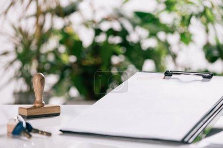 Photo pour Mise au point sélective des clés, timbres et presse-papiers sur bureau blanc, concept hypothécaire - image libre de droit