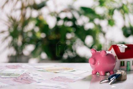 Foto de Enfoque selectivo de billetes, llaves, alcancía y casa modelo en blanco escritorio, concepto de hipoteca - Imagen libre de derechos
