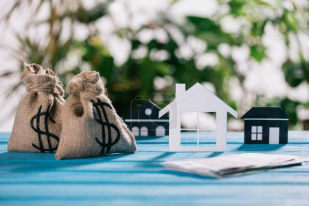 selective focus of paper houses and moneybags with dollar signs on wooden desk, mortgage concept