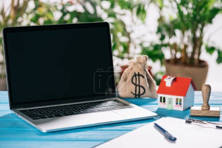 selective focus of pen, clipboard, laptop with blank screen near stamp, house model and moneybag with dollar sign on wooden desk, mortgage concept