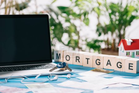 selective focus of laptop with blank screen and keys near headphones, euro banknotes and wooden cubes with letters on desk, mortgage concept