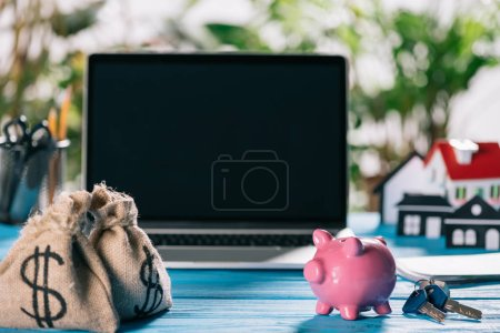 selective focus of moneybags, pink piggy bank and keys on wooden table with laptop on background, mortgage concept