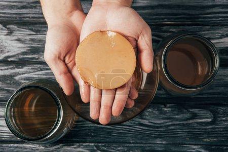top view of bottled tea and kombucha mushroom in hands