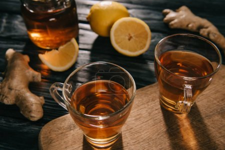 selective focus of  tea in glass cups on wooden chopping board with ginger roots and lemons