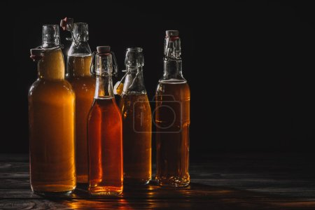 homemade traditional tea in glass bottles isolated on black