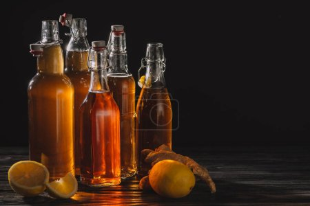 Photo for Homemade organic tea in glass bottles with lemons and ginger root isolated on black - Royalty Free Image