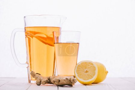 tea with lemon and ginger root in glass and jar on wooden table isolated on white