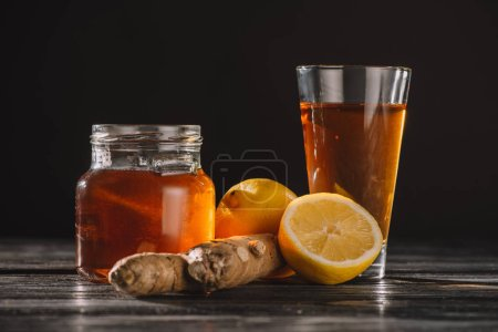 Photo for Tea with lemons and ginger root in jar and glass on wooden table isolated on black - Royalty Free Image