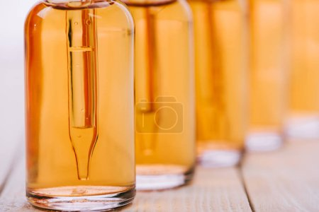 Photo for Selective focus of cbd oil in bottles with dropper on wooden surface isolated on white - Royalty Free Image