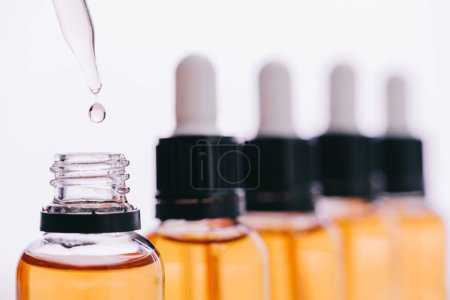 selective focus of cbd oil drop with dropper isolated on white