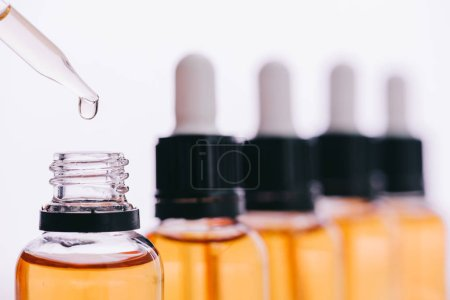 selective focus of cannabidiol oil drop with dropper isolated on white
