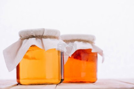 selective focus of bottled natural kombucha mushroom with tea in jars isolated on white