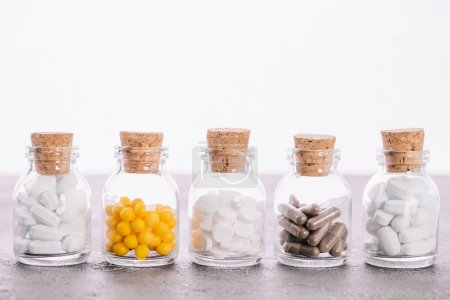 Photo for Row of bottles with corks and different pills isolated on white - Royalty Free Image