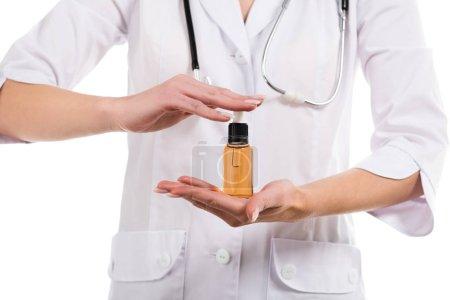 Photo pour Vue recadrée du médecin femelle tenant bouteille avec de l'huile de cbd isolé sur blanc - image libre de droit