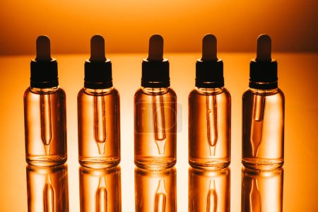 row of cbd oil in bottles with droppers on orange background