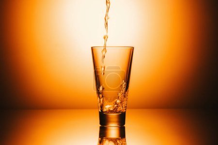 selective focus of empty glass with flowing tea and splash