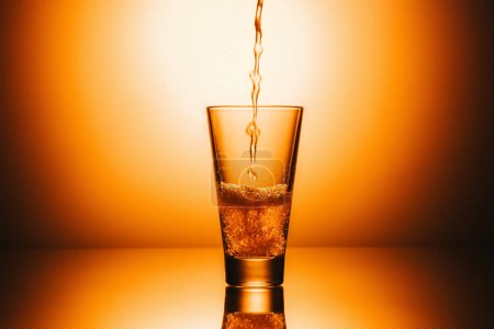 selective focus of glass with flowing tea and splash
