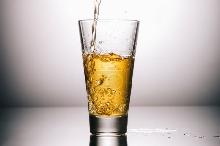 glass of tea and splashes on grey background with copy space