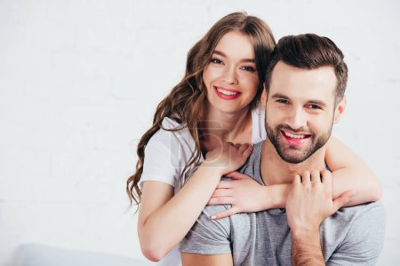 Photo for Adult loving couple gentle embracing and smiling near white wall with copy space - Royalty Free Image