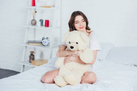 beautiful woman hugging teddy bear and sitting on bed with white bedding