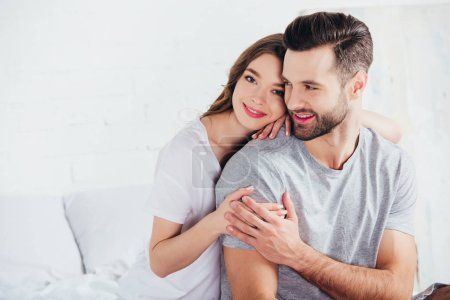 adult happy couple gentle embracing and smiling in bed