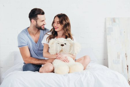 young couple hugging teddy bear while sitting on bed with white bedding
